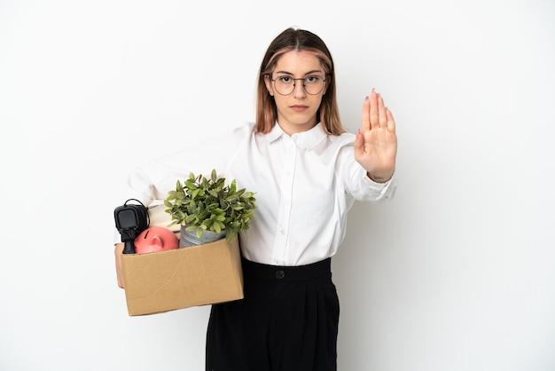 Giovane donna caucasica che si muove nella nuova casa tra scatole isolate su sfondo bianco che fa il gesto di arresto