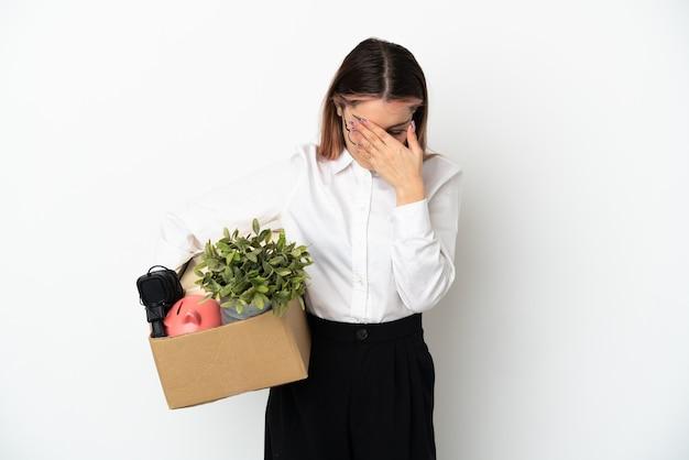 Giovane donna caucasica che si muove in una nuova casa tra scatole isolate su sfondo bianco con espressione stanca e malata