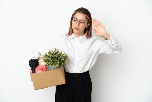 Giovane donna caucasica che si muove nella nuova casa tra scatole isolate sul muro bianco che fa gesto di arresto e deluso