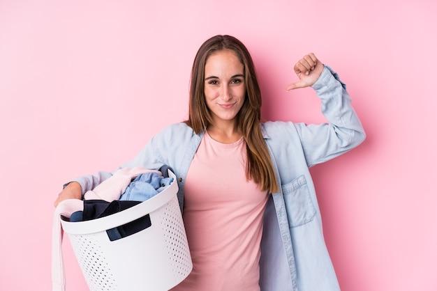 La giovane donna caucasica raccogliendo vestiti sporchi isolati si sente orgogliosa e sicura di sé, esempio da seguire.