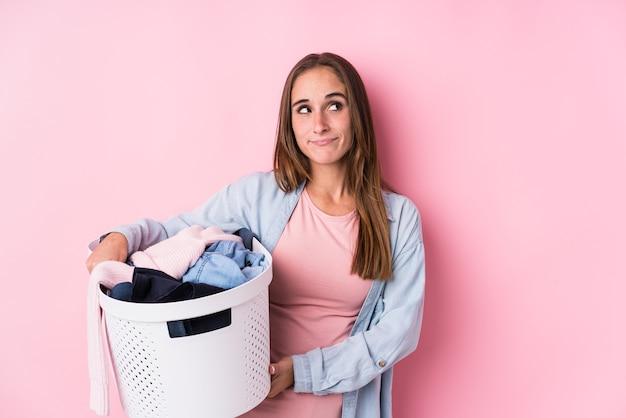 Giovane donna caucasica raccogliendo vestiti sporchi