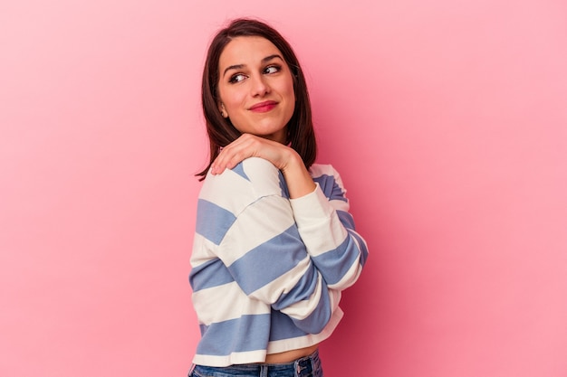 La giovane donna caucasica sugli abbracci rosa del fondo, sorride spensierata e felice.