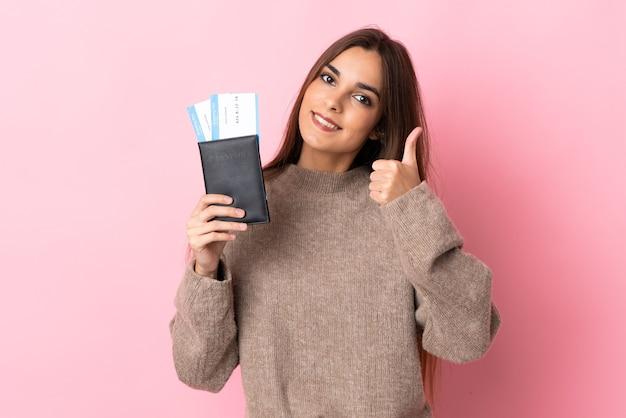 Giovane donna caucasica sul rosa in vacanza in possesso di un passaporto e aereo con il pollice in su
