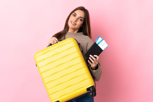 Giovane donna caucasica sul rosa in vacanza con la valigia e il passaporto