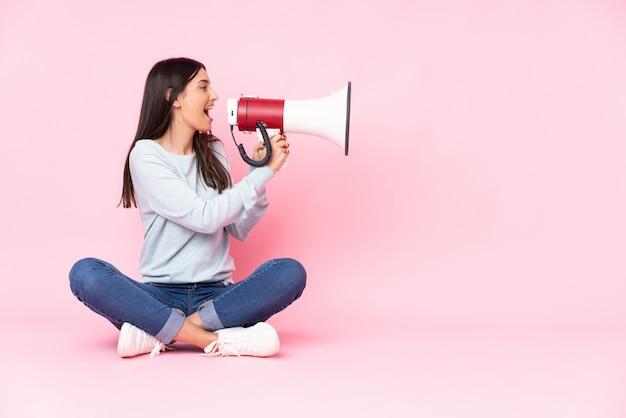 Giovane donna caucasica sulla parete rosa che grida tramite un megafono