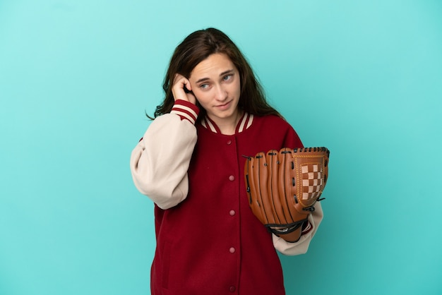 Giovane donna caucasica che gioca a baseball isolata su sfondo blu frustrata e che copre le orecchie