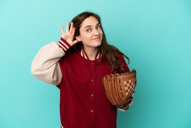 Giovane donna caucasica che gioca a baseball isolata su sfondo blu ascoltando qualcosa mettendo la mano sull'orecchio