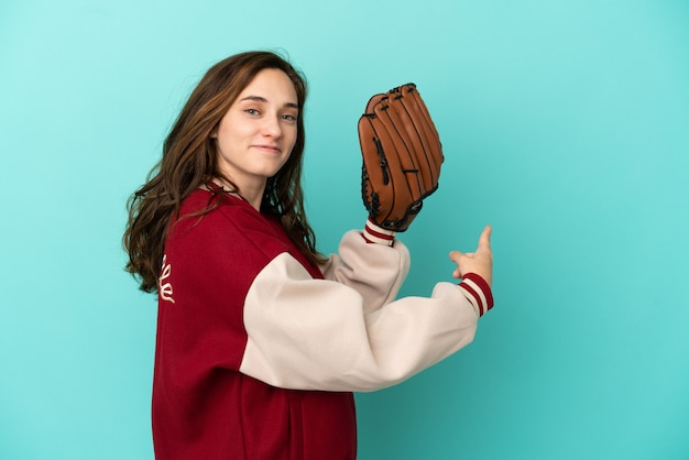 Giovane donna caucasica che gioca a baseball isolata su fondo blu che indica indietro