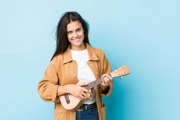 Giovane donna caucasica che gioca ukelele isolato sull'azzurro