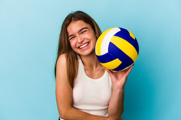 Giovane donna caucasica giocando a pallavolo isolato su sfondo blu ridendo e divertendosi.