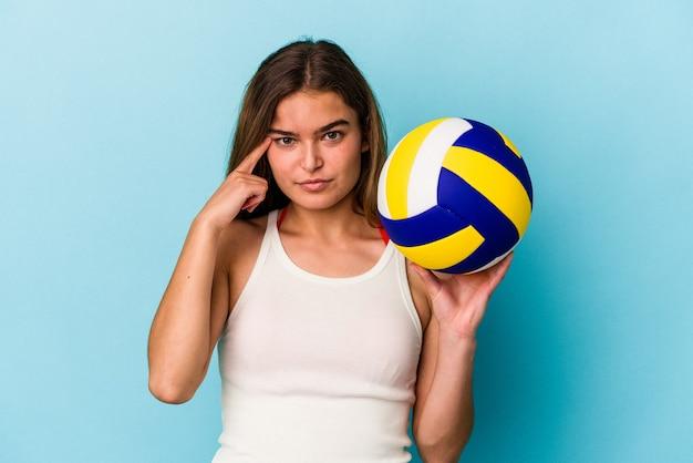 Giovane donna caucasica che gioca a pallavolo isolata su sfondo blu che punta il tempio con il dito, pensando, concentrata su un compito.