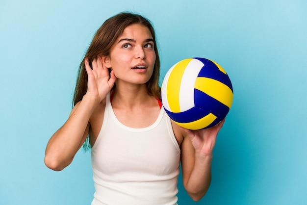 Giovane donna caucasica giocando a pallavolo isolato su sfondo blu cercando di ascoltare un pettegolezzo.