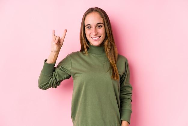 Giovane donna caucasica in posa isolato mostrando un gesto di corna come un concetto di rivoluzione.