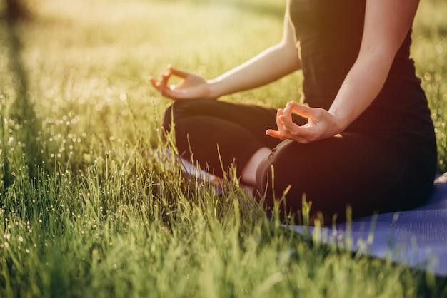La giovane donna caucasica pratica l'yoga nella posizione di loto su una mattina soleggiata in anticipo in una foresta con il fuoco selettivo molle della rugiada e dell'erba.