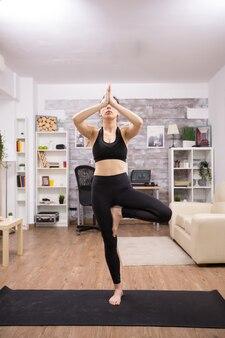Giovane donna caucasica che pratica la posa di yoga dell'albero che indossa abbigliamento sportivo nero in casa.
