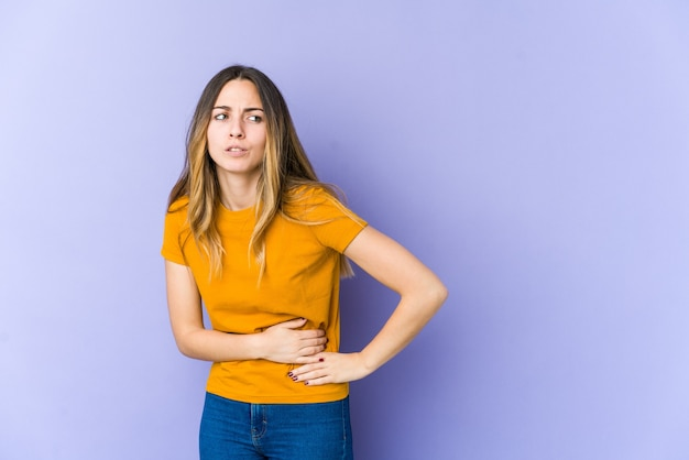 Giovane donna caucasica sulla porpora che ha un dolore al fegato, mal di stomaco.