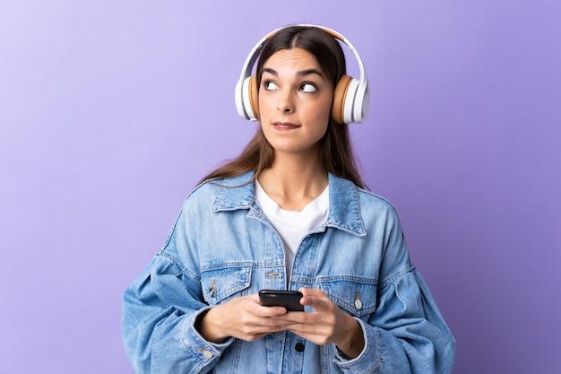Giovane donna caucasica sulla musica d'ascolto viola con un cellulare e un pensiero