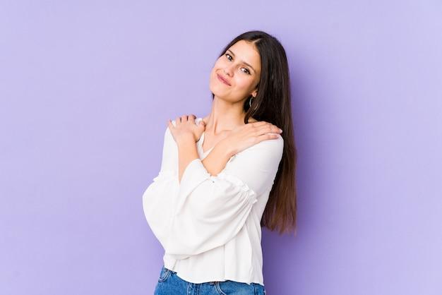 Giovane donna caucasica sugli abbracci viola della parete, sorridente spensierato e felice.