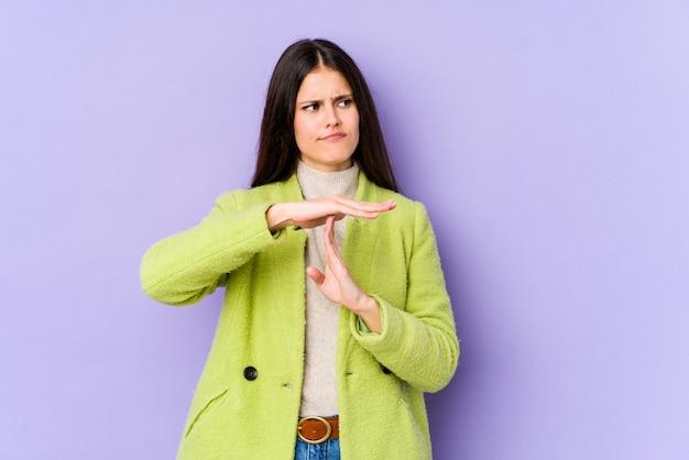 Giovane donna caucasica sulla parete viola che mostra un gesto di timeout.