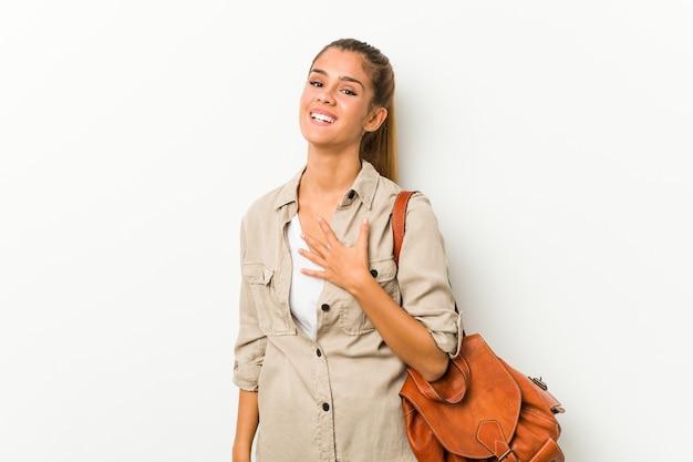 La giovane donna caucasica pronta per un viaggio ride ad alta voce tenendo la mano sul petto.