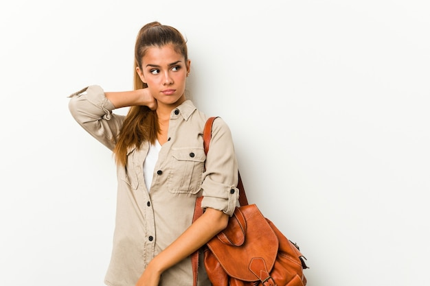 Giovane donna caucasica pronta per un viaggio toccando la parte posteriore della testa, pensando e facendo una scelta.
