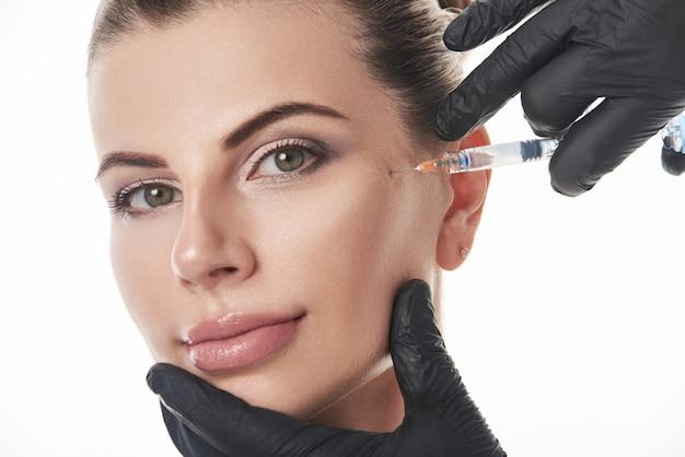 Giovane donna caucasica che riceve un trattamento cosmetico anti invecchiamento con iniezione di siringa.