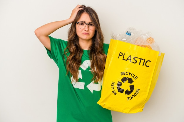 Giovane donna caucasica che ricicla un pieno di plastica isolata su sfondo bianco scioccata, ha ricordato un incontro importante.