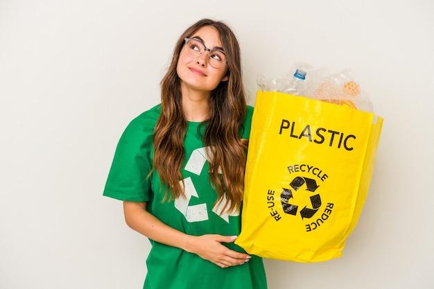Giovane donna caucasica che ricicla un pieno di plastica isolato su sfondo bianco sognando di raggiungere obiettivi e scopi