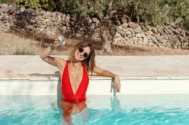 Giovane donna caucasica in costume da bagno rosso rilassante vicino a una piscina con un cocktail tropicale