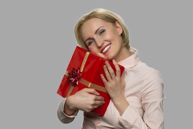 Giovane donna caucasica che si rallegra della sua confezione regalo di compleanno. donna allegra abbracciando confezione regalo contro uno sfondo grigio.