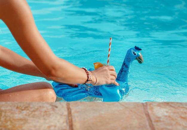 Giovane donna caucasica rilassante con cocktail tropicale vicino a una piscina