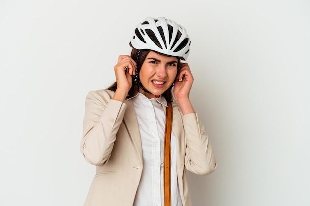 Giovane donna caucasica in sella a una bicicletta per lavorare isolato su sfondo bianco che copre le orecchie con le mani.