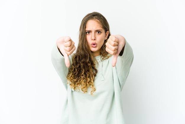 Giovane donna caucasica che mostra il pollice verso il basso ed esprime antipatia.