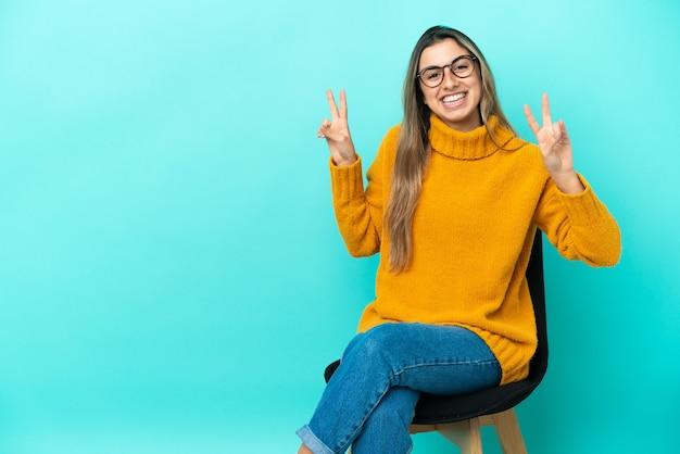 Giovane donna caucasica seduta su una sedia isolata su sfondo blu che mostra il segno della vittoria con entrambe le mani