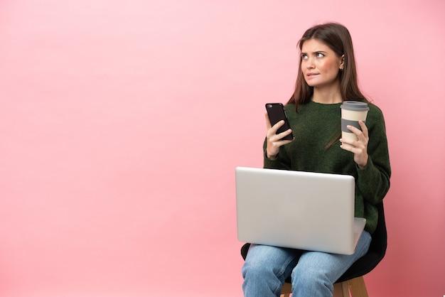 Giovane donna caucasica seduta su una sedia con il suo laptop isolato su sfondo rosa tenendo il caffè da portare via e un cellulare mentre si pensa a qualcosa