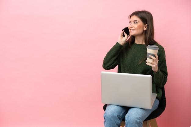 Giovane donna caucasica seduta su una sedia con il suo laptop isolato su sfondo rosa tenendo il caffè da portare via e un cellulare