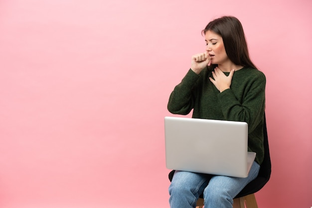 La giovane donna caucasica seduta su una sedia con il suo computer portatile isolato su sfondo rosa soffre di tosse e si sente male