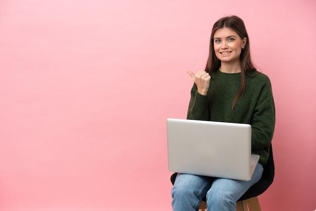 Giovane donna caucasica seduta su una sedia con il suo computer portatile isolato su sfondo rosa che punta di lato per presentare un prodotto