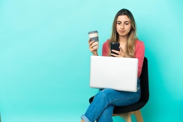 Giovane donna caucasica seduta su una sedia con il suo pc isolato su sfondo blu tenendo il caffè da portare via e un cellulare