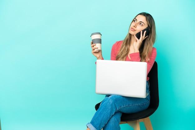 Giovane donna caucasica seduta su una sedia con il suo pc isolato su sfondo blu che tiene il caffè da portare via e un cellulare