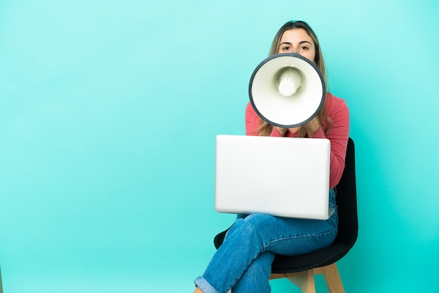 Giovane donna caucasica seduta su una sedia con il suo pc isolato su sfondo blu che grida attraverso un megafono