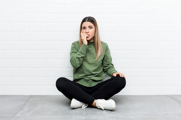 Giovane donna caucasica che si siede sul pavimento mordendosi le unghie, nervosa e molto ansiosa.