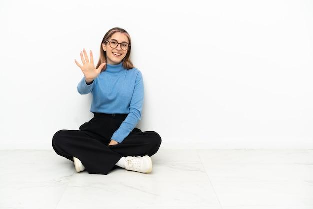 Giovane donna caucasica seduta sul pavimento contando cinque con le dita