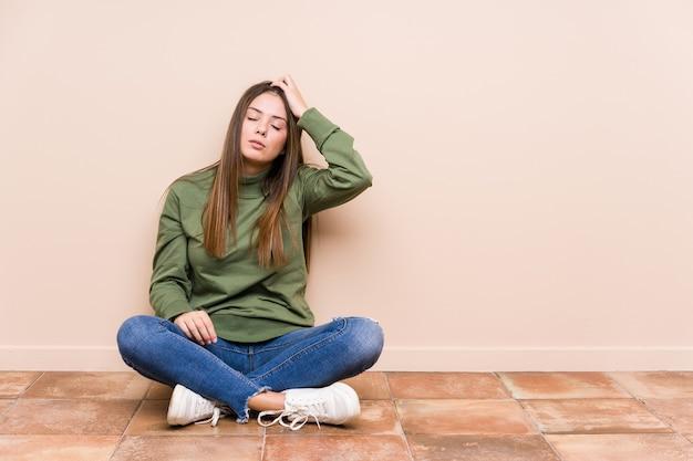 Giovane donna caucasica seduta sul pavimento isolata di essere scioccata, ha ricordato un incontro importante.