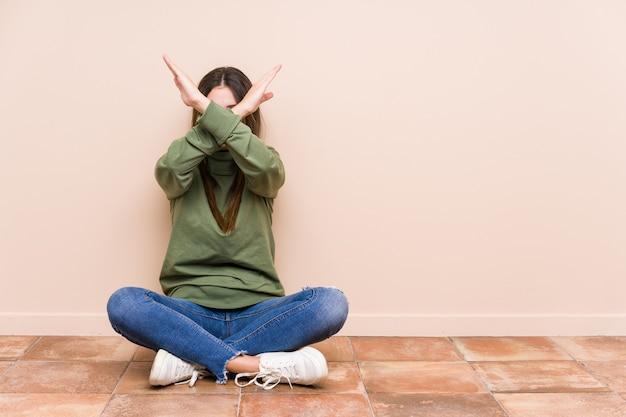 Giovane donna caucasica seduta sul pavimento isolato mantenendo due braccia incrociate, concetto di negazione.