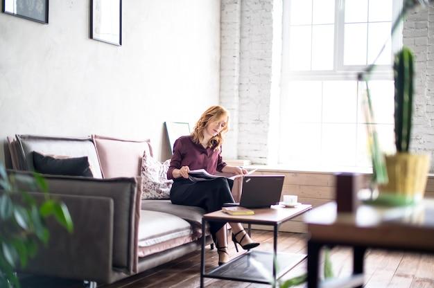 Giovane donna caucasica seduta sul divano, lavorando presso un ufficio moderno. sul tavolo ci sono laptop, notebook e tazza di caffè. concetto di affari