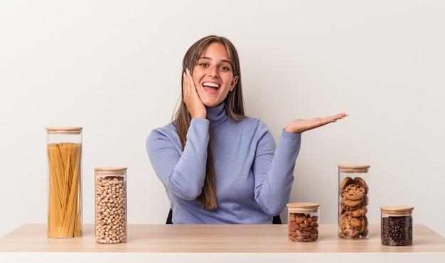 La giovane donna caucasica seduta a un tavolo con una pentola per alimenti isolata su sfondo bianco tiene lo spazio della copia su un palmo, tiene la mano sulla guancia. stupito e deliziato.
