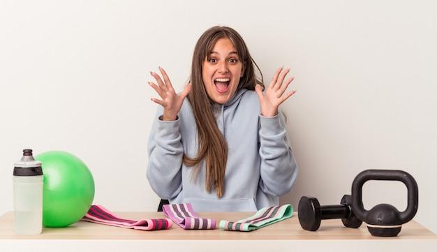 Giovane donna caucasica seduta a un tavolo con attrezzatura sportiva isolata su sfondo bianco che celebra una vittoria o un successo, è sorpreso e scioccato.
