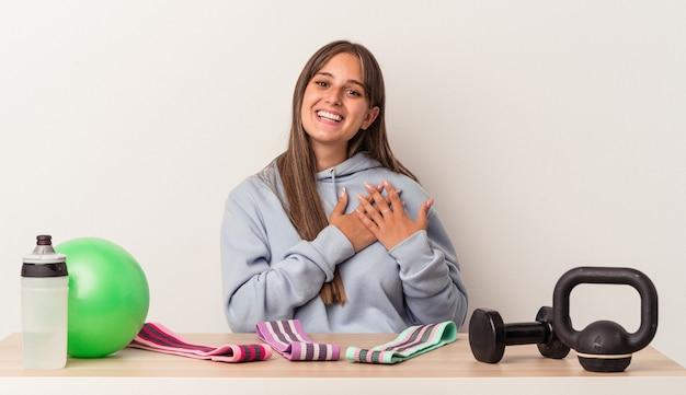La giovane donna caucasica seduta a un tavolo con attrezzature sportive isolate su sfondo bianco ha un'espressione amichevole, premendo il palmo sul petto. concetto di amore.
