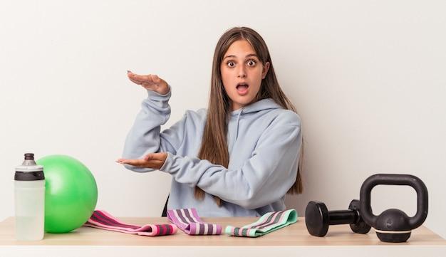 Giovane donna caucasica seduta a un tavolo con attrezzatura sportiva isolata su sfondo bianco scioccata e stupita in possesso di uno spazio di copia tra le mani.
